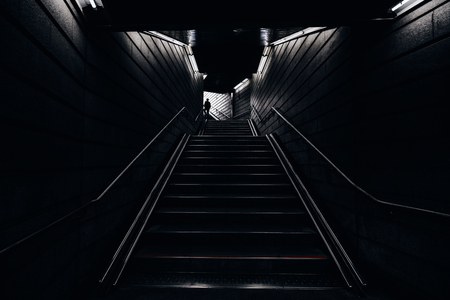 Man walking into the light in the dark tunnel from underground