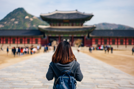 Young asian woman traveler with backpack traveling into the Gyeongbokgung Palace  with blue sky and clouds at Seoul city, South Korea.