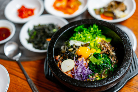 Traditional Korean dish, rice with vegetables and beef its call Bibimbap. Bibimbap rice stone bowl,stone-roasted. Фото со стока