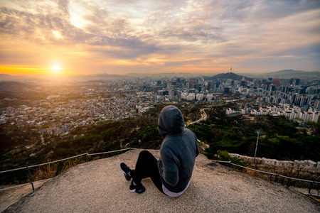 Young woman traveler sitting on the rock looking sunrise scene of Seoul downtown city skyline, View of N Seoul Tower at Namsan Park in best viewpoint from inwangsan mountain in Seoul city, South Korea