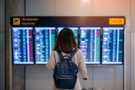 Young woman traveler with backpack and luggage looking at boarding time at departure board at terminal in international airport
