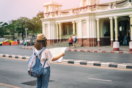 Young asian woman traveler with backpack and hat standing and looking for search way for travel at train station in Bangkok city Thailand. Traveling in Bangkok Thailand