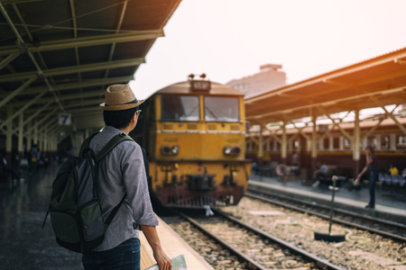Young asian man traveler with backpack and hat standing and holding map waiting train for travel at train station in Bangkok city Thailand. Traveling in Bangkok Thailand 版權商用圖片