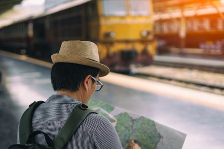 Young asian man traveler with backpack and hat sitting and looking map for search the way for travel at train station in Bangkok city Thailand. Traveling in Bangkok Thailand 版權商用圖片
