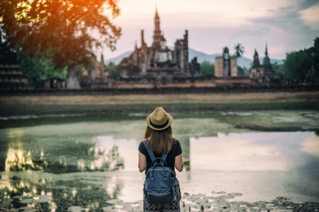 Young woman hipster backpacker traveling into Wat Mahathat temple in the Sukhothai Historical Park contains the ruins of old Sukhothai, Thailand 版權商用圖片