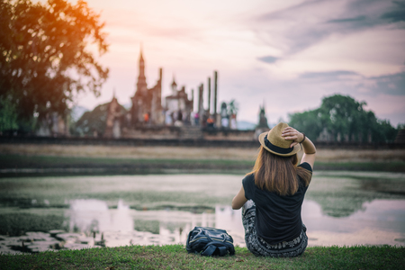 Young woman hipster backpacker traveling into Wat Mahathat temple in the Sukhothai Historical Park contains the ruins of old Sukhothai, Thailand, UNESCO world Heritage Site. 版權商用圖片