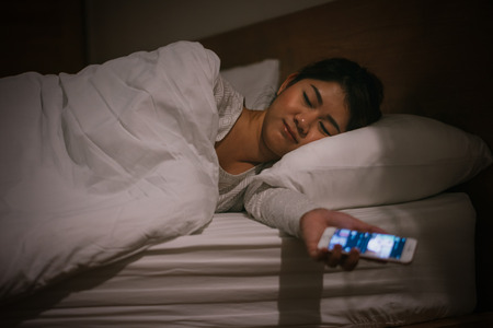 Young asian woman sleep on bed late at night holding mobile phone and tired in internet communication overuse and smartphone addiction. Фото со стока