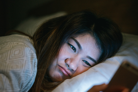Young asian woman on bed late at night texting using mobile phone sleepy and tired in internet communication overuse and smartphone addiction with boring emotion. Фото со стока
