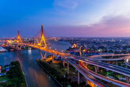 Aerial view of Bhumibol suspension bridge in Bangkok city with light trails of car on the road at sunset sky and clouds in Bangkok Thailand.