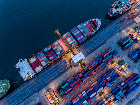 Aerial view of international port with Crane loading containers in Container ship in import export and business logistics with crane and Shipping cargo.