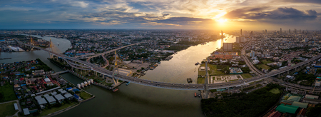Aerial view panorama of Bhumibol suspension bridge cross over Chao Phraya River in Bangkok city with car on the bridge at sunset sky and clouds in Bangkok Thailand. Stockfoto