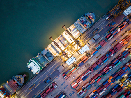 Top view of international port with Crane loading containers in import export business logistics at night.