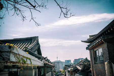 Traditional korean style architecture in Bukchon Hanok Village with N Seoul Tower on Namsan mountain in background at Seoul, South Korea.