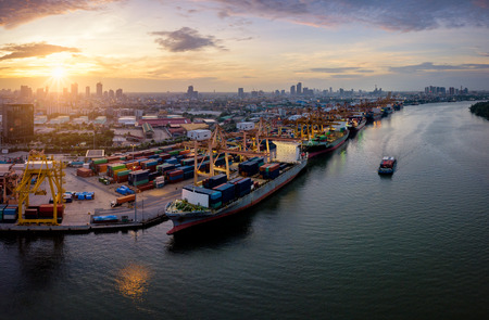 Aerial view of international port with Crane loading containers in import export business logistics with cityscape of Bangkok city Thailand at sunrise