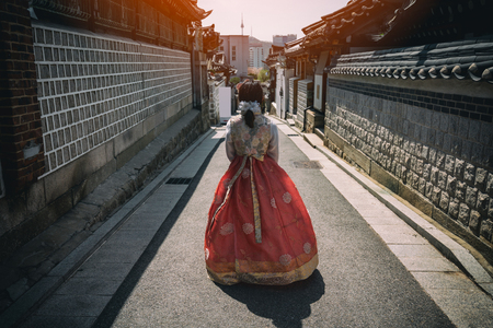Young woman traveler in traditional korean dress or call hanbok traveling into  Bukchon Hanok Village with N Seoul Tower on Namsan mountain in background at Seoul, South Korea.