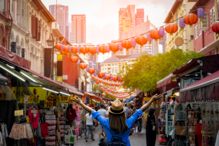 Young woman traveler with backpack and hat traveling into Chinatown at singapore city downtown. Travelling in Singapore concept 報道画像