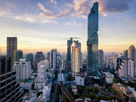 Aerial view of Bangkok skyline and skyscraper on Silom road center of business in capital. Modern city and BTS skytrain with Chao Phraya river at Bangkok Thailand on sunrise Stockfoto