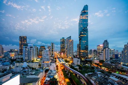 Luchtfoto van de skyline van Bangkok en wolkenkrabber met BTS skytrain Bangkok het centrum. Panorama van de zakenwijk Sathorn en Silom Bangkok Thailand 's nachts.