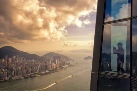 Young man traveler take a photo of Hong Kong City skyline at sunset  from sky 100 Hongkong.