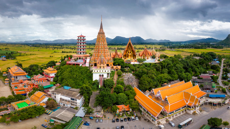 Aerial view of Wat Tham Sua Temple with rice fields in Kanchanaburi Province, Thailand. Stockfoto