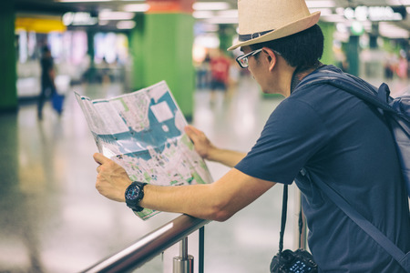 Young man asian traveler looking map at Hong Kong subway station MTR Stockfoto