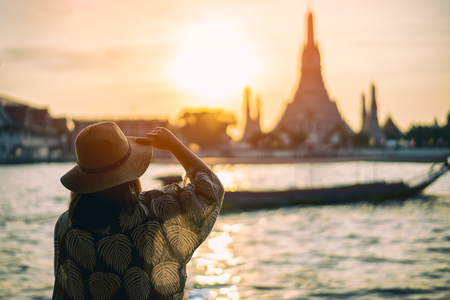 Young woman traveler traveling into Wat Arun Ratchawararam Ratchawaramahawihan Temple in bangkok, Thailand at sunset