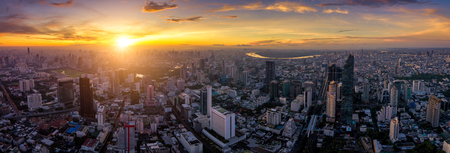 Aerial view of Bangkok skyline panorama and skyscraper with light trails on Silom road center of business in capital. Modern city and BTS skytrain with Chao Phraya river at Bangkok Thailand on sunrise