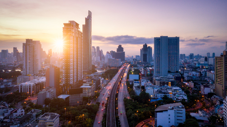 Aerial view of Bangkok skyline panorama and skyscraper with light trails on Sathorn Road center of business in capital. Modern buildings condominium at Chao Phraya River Bangkok Thailand at sunrise.