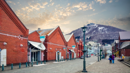 Cityscape of the historic red brick warehouses and Mount Hakodate Ropeway at sunset on Hakodate Mountain at Hakodate near Sapporo, Hokkaido Japan at winter
