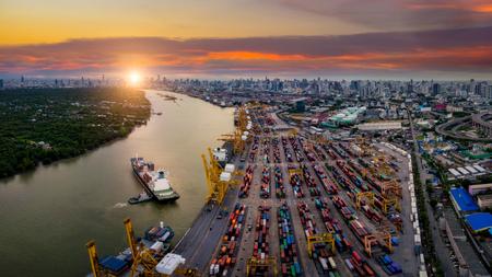 Vue aérienne du port international avec des conteneurs de chargement de grue dans la logistique commerciale d'import-export avec le paysage urbain de la ville de Bangkok en Thaïlande au coucher du soleil