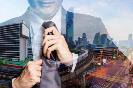 Double exposure of young happy businessman with black suit adjusting his necktie with Cityscape of bangkok city and BTS Skytrain in concept start new life and new job in the city background. Stockfoto