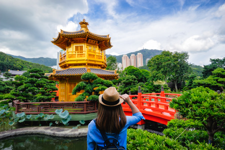 Young woman traveler traveling into Hongkong beautiful golden teak wood pagoda at Nan Lian Garden in Hong Kong