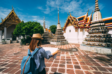 Young woman traveler with backpack and hat looking the Map in Wat Pho at Bangkok Thailand. Traveling in Bangkok Thailand