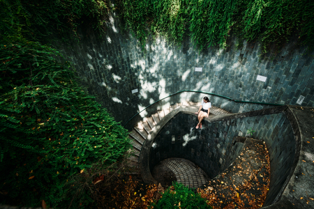 Young girl traveler sitting on circle stairs of a spiral staircase of an underground crossing in tunnel at Fort Canning Park, Singapore Stockfoto