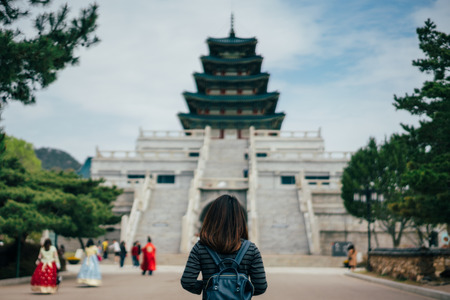 Young asian woman traveler with backpack traveling into the Gyeongbokgung Palace  with green tree in background at Seoul city, South Korea.