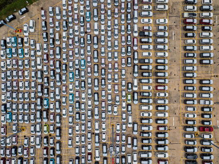 Top view of many new car lined up in row waiting send to dealer outside an automobile factory and waiting for export to other country.