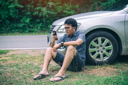 Young asian handsome man sitting on the floor by the broken down car and waiting for help with strain face and serious while using smartphone