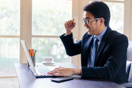 Young happy businessman using his laptop and glad while Raise a fist up on office desk. Portrait of business executive man using laptop in office with successful.