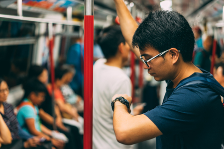 Young man traveler is visiting at Hongkong by subway MTR train and looking watch. The Mass Transit Railway is the rapid transit railway system in Hong Kong.