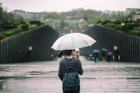 Young asian woman traveler in lonely feeling holding umbrella traveling in Ewha womans university at Seoul, South Korea at rainy day. Ewha womans university is the famous place at Seoul city.