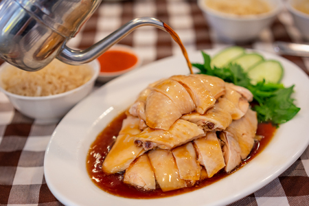 Asian Chinese food style Steam Chicken with Rice and sauce (Hainan Chicken) on white plate at Chinese restaurant in Singapore Stockfoto