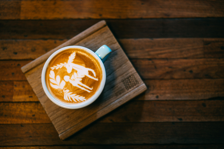 Top view of a cup of coffee latte with beautiful latte art on wooden table. Stockfoto