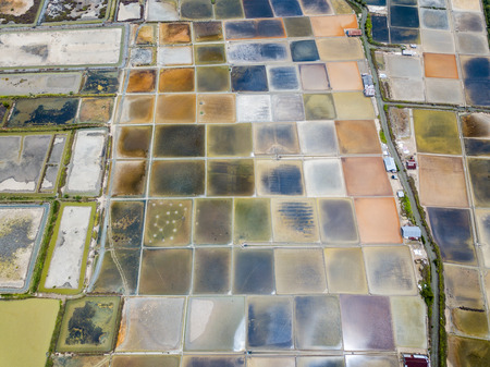 Aerial view of saline pond and salt evaporation ponds filled from ocean salt crystals  have colourful and vivid