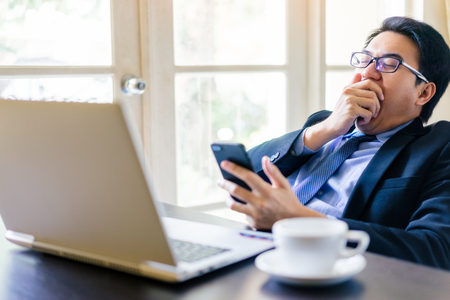 Young happy businessman using his smartphone and sleepy while gag on office desk. Portrait of business executive man using laptop in office on lazy day. Stockfoto