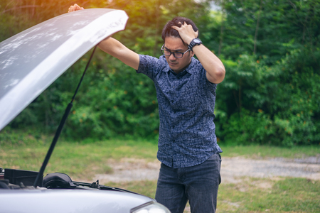 Young asian handsome man standing by the broken down car and waiting for help with strain face and serious Stockfoto