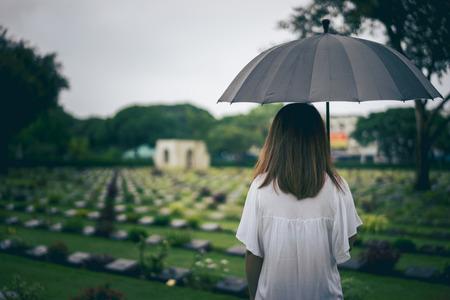 Junge Frau mit schwarzem Regenschirm trauert auf dem Friedhof