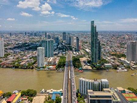 Aerial view of Bangkok skyline and skyscraper with BTS skytrain Bangkok downtown. Panorama of Sathorn and Silom business district Bangkok Thailand with blue sky and clouds.