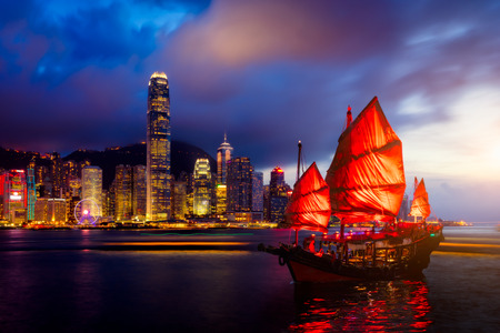 Hong Kong City skyline with tourist sailboat at night. View from across Victoria Harbor Hong Kong. Imagens
