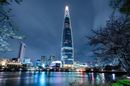 Cityscape of Seoul downtown city skyline with cherry blossom at night, Aerial view of skyscraper at Seokchon Lake at nightand sakura around lake. The amazing modern building at Seoul city, South Korea Redactioneel