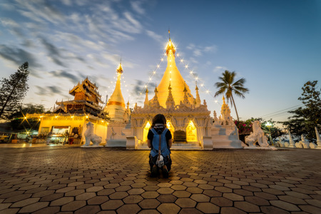 Young woman traveler sitting while praying with white pagoda at Wat Phra That Doi Kong Mu Temple in Mae Hong Son province near Chiang Mai, Thailand